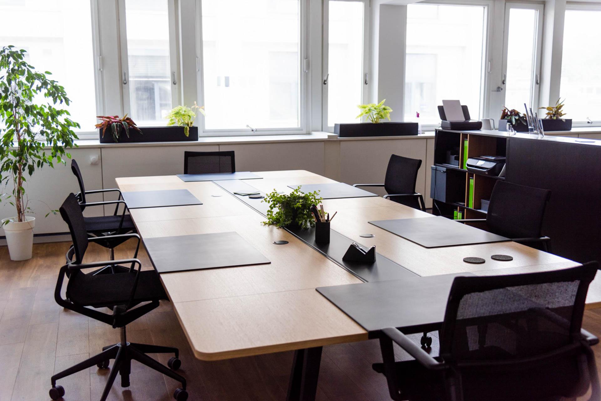 Ein Arbeitsplatz für 6 Personen in einem Großraumbüro. Unterlagen, Büromaterial und Zimmerpflanzen schmücken den Schreibtisch. Rechts im Bild ein Regal als Raumteiler, in dem ein Drucker und ein Fax stehen.