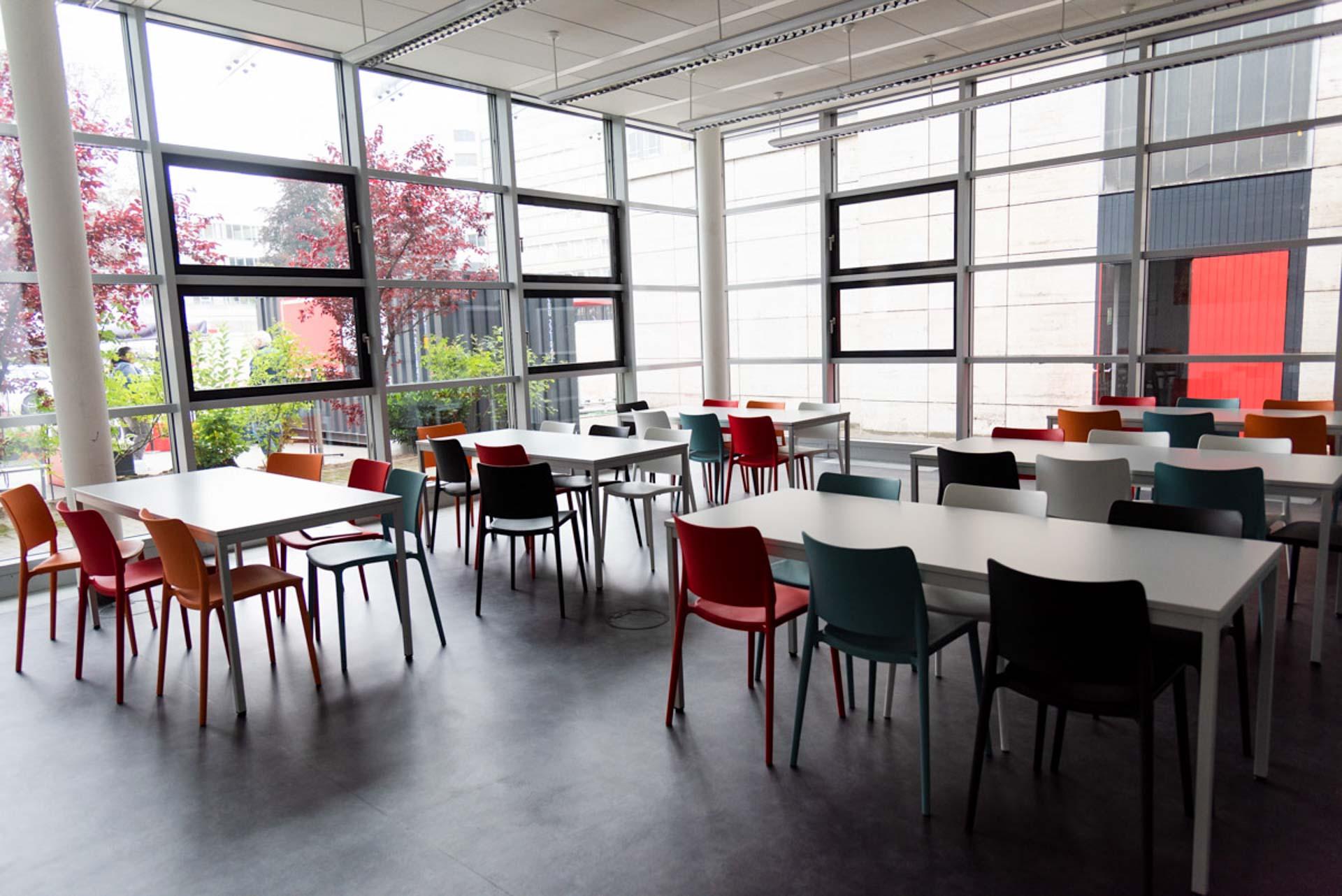 Kantine des Quartier231 mit Blick nach draußen. Der Raum ist vollverglast mit Blick auf den Food Corner, an weißen Tischen können bis zu sechs Personen auf pastellfarbenen Stühlen platznehmen.
