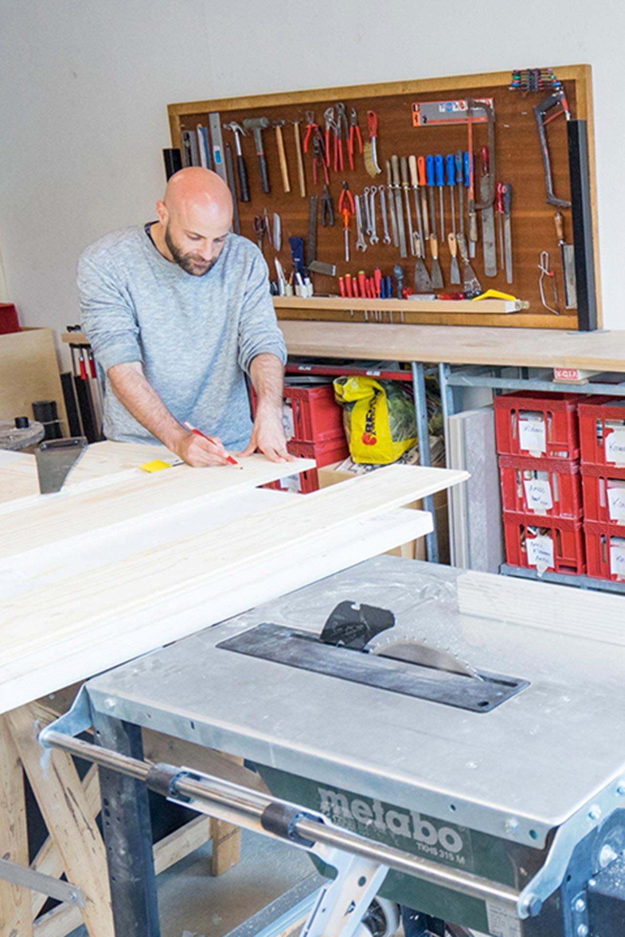 Ein zu einem Werkraum umgewandeltes Studio im Quartier231. Ein Mann schneidet Holz an seiner Tischkreissäge (Metabo TKHS 315 M) zurecht. Im Hintergrund hängt ein voll bestücktes Werkzeugregal oberhalb einer Arbeitsplatte