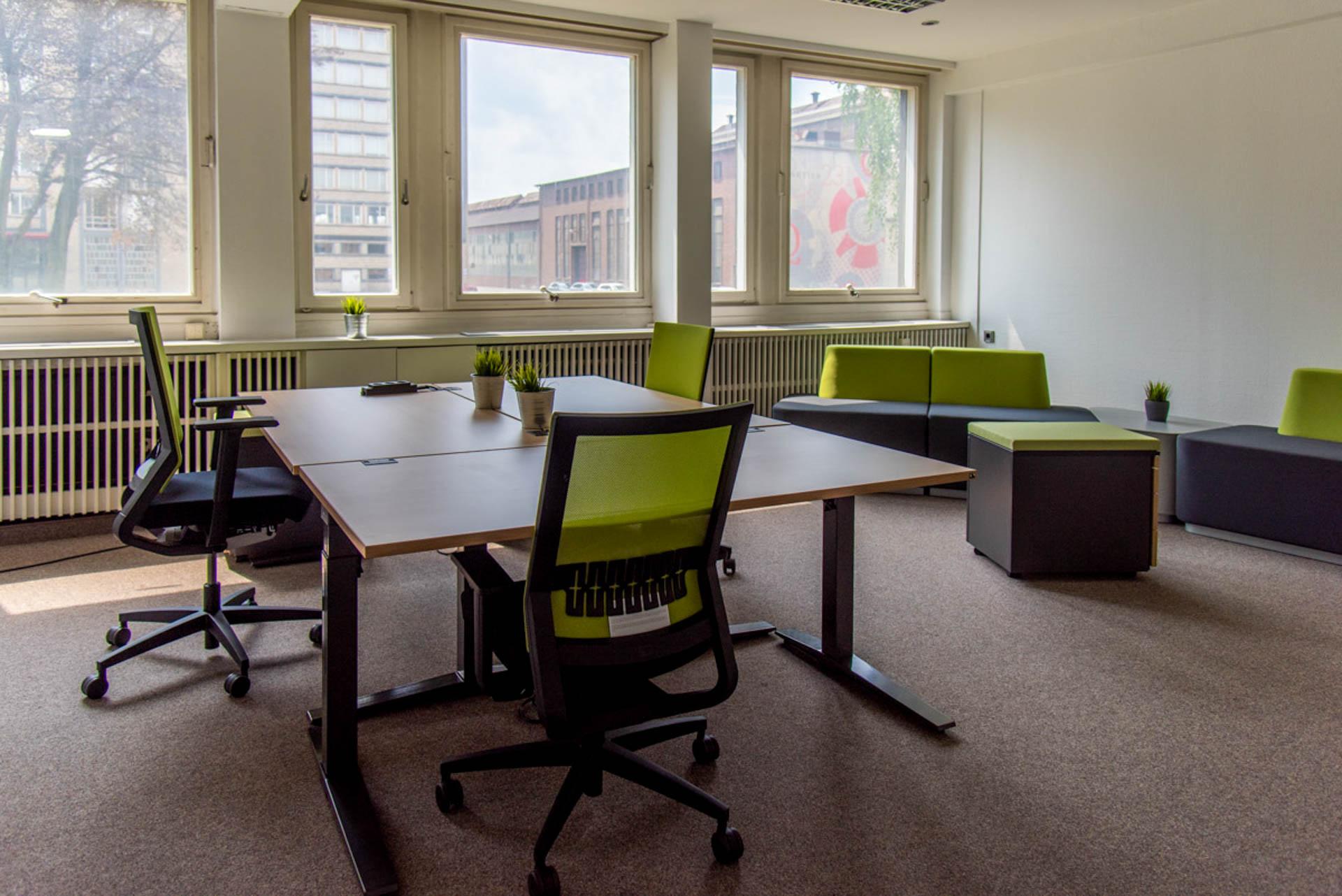 Ein Coworking Space in Oberhausen. ein helles Büro mit Sofas als Ruhepunkte in den Ecken, während im Zentrum ein aus drei Schreibtischen zusammengestellter Arbeitsplatz steht. Um ihn herum Drehstühle mit grüner Sitzbespannung.