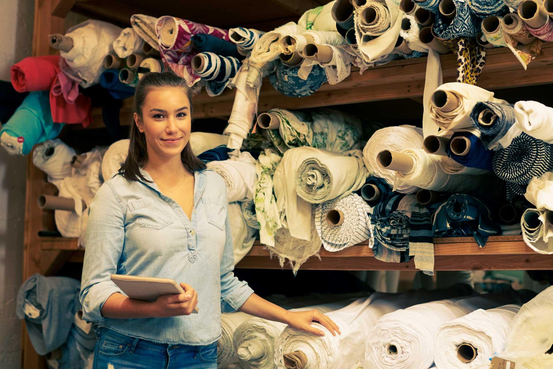 Eine junge Unternehmerin mit einem Tablet in der Hand steht vor einem Lagerregal voller Stoffbahnen.