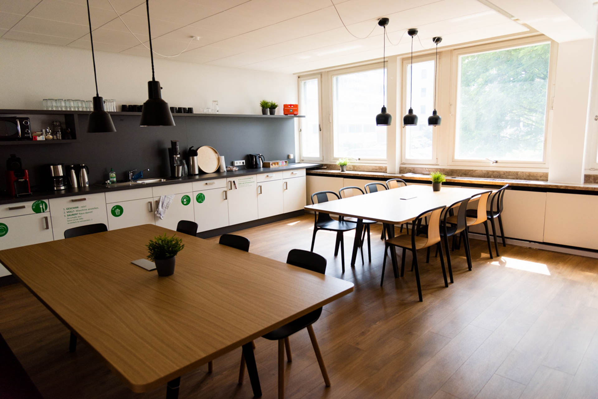 Open Space im Quartier231. Auf Parkettboden stehen zwei für jeweils 8 Personen Platz bietende Tische, von ebensovielen Stühlen umstellt. Links im Raum ist eine Küchenzeile mit Thermoskannen, Wasserkochern, einer Spülmaschine, Besteckschublade, einem Tablett und weiteren Küchenutensilien zu sehen. Über den Tischen hängen unter schwarzen Metallschirmen drei respektive zwei Lampen.