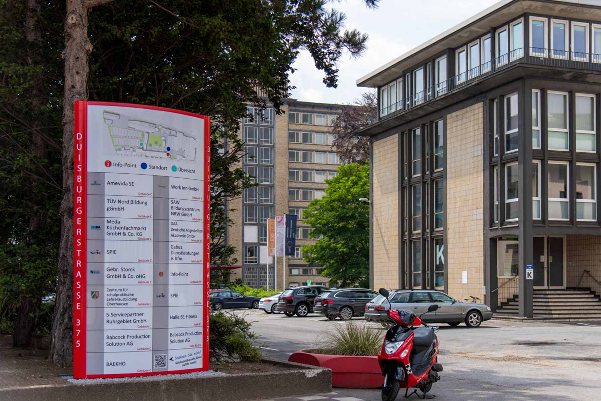 Der Wegweiser mit Geländeplan vor Gebäude K.